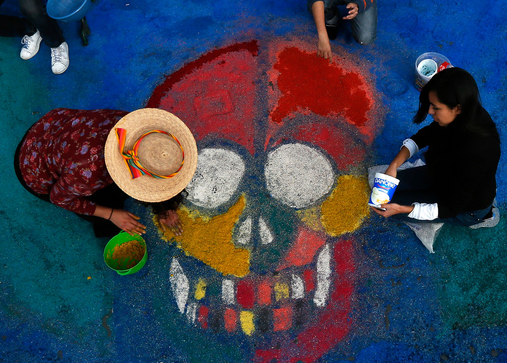 . Residents create a sawdust representation of a skull during Day of the Dead festivities in Mexico City, Thursday, Oct. 27, 2016. The holiday honors the dead as friends and families gather in cemeteries to decorate their loved ones\' graves and hold vigil through the night on Nov. 1 and 2. (AP Photo/Marco Ugarte)