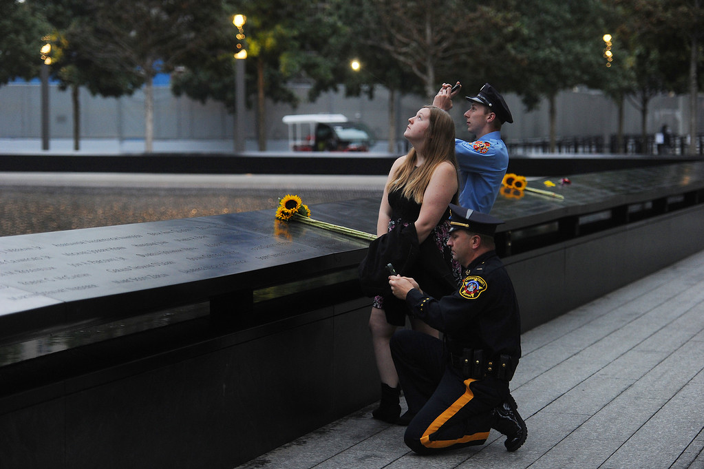 . Family members, from left, Mitch, Maggie and Zach Ellicott , from New Jersey , take photos of the new 1 World Trade Center from the North Pool during memorial observances on the 13th anniversary of the Sept. 11 terror attacks on the World Trade Center in New York, Thursday, Sept. 11, 2014. (AP Photo/The Daily News, Robert Sabo, Pool)