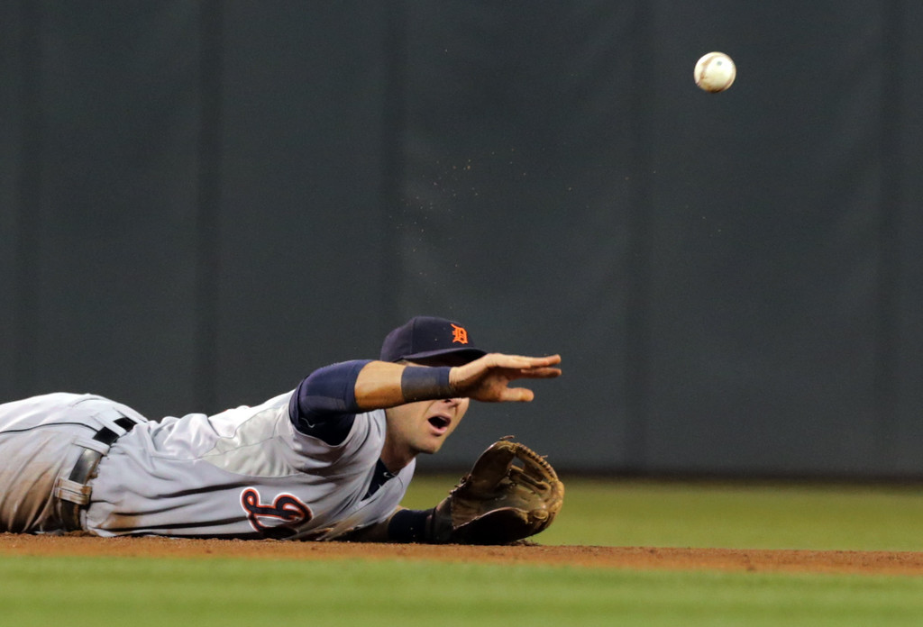 . Detroit Tigers shortstop Andrew Romine tosses the ball from the turf to second baseman Ian Kinsler in time to put out Minnesota Twins center fielder Aaron Hicks on a fielder\'s choice hit into by Jordan Schafer in the fifth inning of a baseball game, Tuesday, Sept. 16, 2014, in Minneapolis. (AP Photo/Jim Mone)