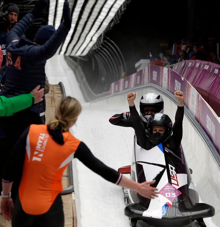 . The team from the United States USA-2, piloted by Jamie Greubel with brakeman Aja Evans, cross into the finish area to win the bronze medal in the women\'s bobsled competition at the 2014 Winter Olympics, Wednesday, Feb. 19, 2014, in Krasnaya Polyana, Russia. (AP Photo/Michael Sohn)