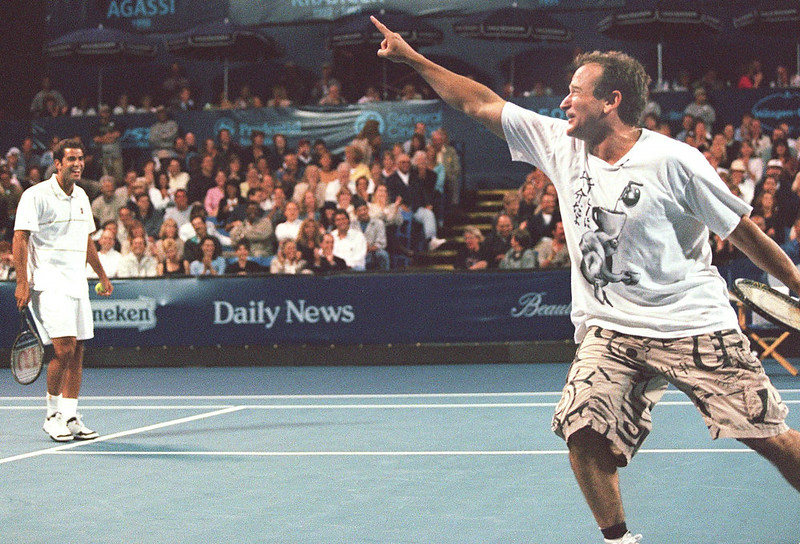 . US comedian Robin Williams(R) celebrates with doubles partner Pete Sampras(L) after hitting a winning volley past Andre Agassi at the University of California-Los Angeles 26 July 1999. Sampras and Williams played Agassi and US comedian Billy Crystal in a 15-minute charity match which opened the 8th Annual Mercedes-Benz Cup.   LUCY NICHOLSON/AFP/Getty Images