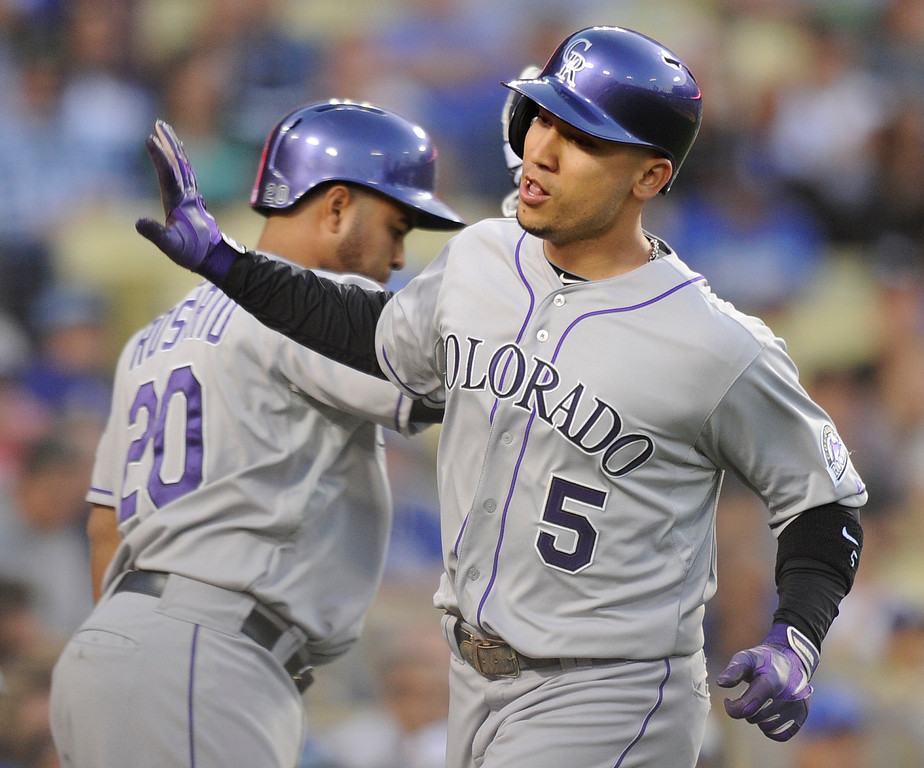. Rockies #5 Carlos Gonzalez is congratulated by #20 Wilin Rosario after he scored on a sacrifice fly by Michael Cuddyer in the first inning. The Los Angeles Dodgers played host to the Colorado Rockies in a game at Dodger Stadium in Los Angeles, CA 5/1/2013(John McCoy/Staff Photographer)