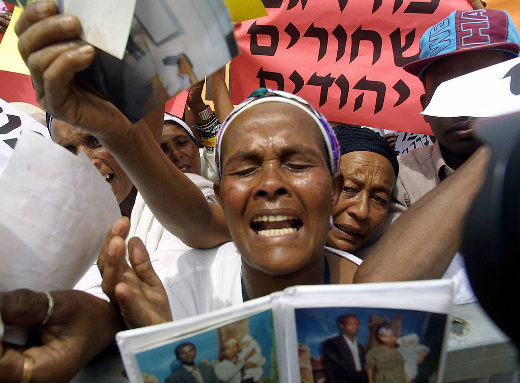 . Ethiopian Jewish women cry as they hold up pictures of their relatives, who are still in Ethiopia, during a demonstration in front of the Israeli prime minister Ariel Sharon\'s office in Jerusalem 25 may 2003. Some 500 Ethiopian Jews held a protest calling on the government to bring some 20,000 of their relatives from Ethiopia to Israel and for the end of discrimination against their community.   OREL COHEN/AFP/Getty Images