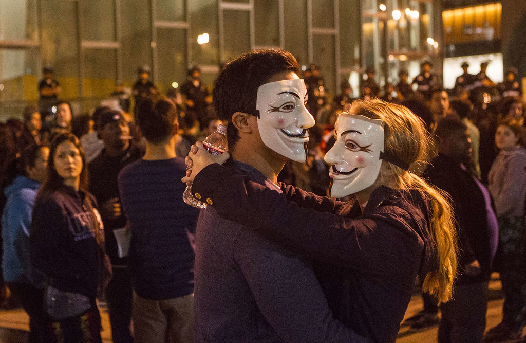 . Demonstrators wearing Guy Fawkes mask are seen in front of Los Angeles police headquarters on November 25, 2014 in Los Angeles during demonstrations against a decision by a Ferguson, Missouri grand jury to not indict a white police officer in the shooting of black teenager Michael Brown.  Violent protests and looting erupted in the US town of Ferguson for a second day after the grand jury\'s decision. AFP PHOTO / Ringo CHIU/AFP/Getty Images