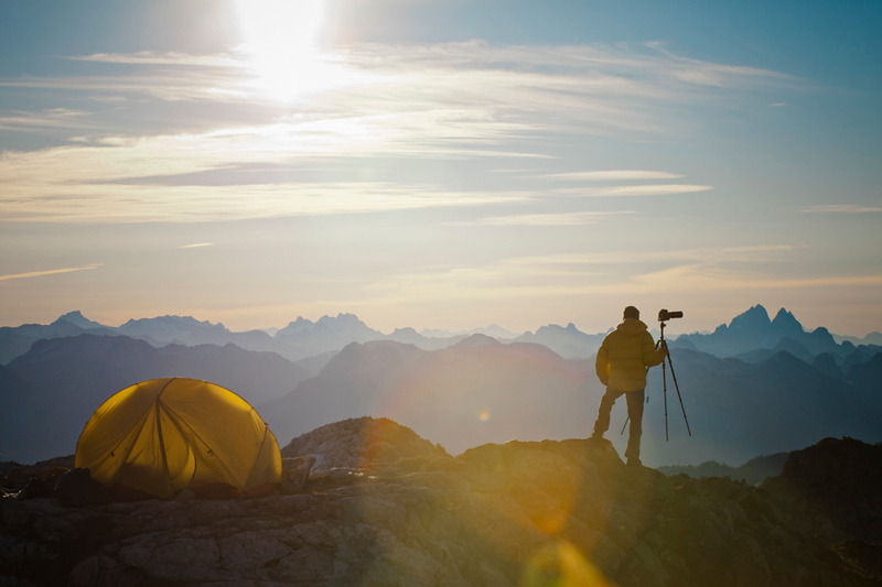 A photographer enjoys the view of the sunrise from his campsite on a rocky mountain ridge.