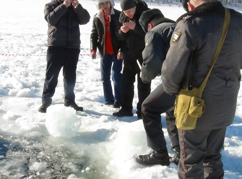 Description of . A handout photo taken on February 15, 2013, and provided by Chelyabinsk region police department shows police officers examining small objects as they stand near a six-metre (20-foot) hole in the ice of a frozen lake, reportedly the site of a meteor fall, outside the town of Chebakul in the Chelyabinsk region. Divers scoured today  the bottom of a Russian lake for fragments of a meteorite that plunged to Earth in a blinding fireball whose shockwave injured 1,200 people and damaged thousands of homes. AFP PHOTO / CHELYABINSK REGION POLICE DEPARTMENT