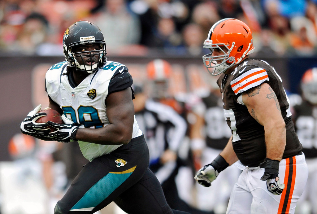 . Jacksonville Jaguars defensive tackle Sen\'Derrick Marks, left, runs from Cleveland Browns guard John Greco after recovering a fumble by Browns quarterback Brandon Weeden in the second quarter of an NFL football game on Sunday, Dec. 1, 2013, in Cleveland. (AP Photo/David Richard)