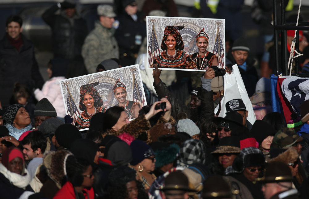 Description of . People hold aloft posters of President Barack Obama and first lady Michelle Obama, altered to appear in African dress, during the inauguration parade on January 21, 2013 in Washington, DC. President Obama was ceremonially sworn in for a second term office during a public ceremony at the U.S. Capitol building.  (Photo by John Moore/Getty Images)