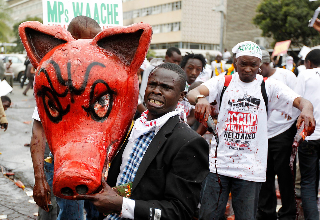 . A protester carrying a dummy pig head covered with animal blood, reacts as he participates in a demonstration against lawmakers\' demands for a pay rise, outside parliament buildings in Nairobi, June 11, 2013. Refusing to accept a cut imposed by the Salaries and Remuneration Commission in May, members of parliament voted to increase their salaries to 130 times the minimum wage, which according to them, are needed to deter bribery and provide charitable support for constituents. Protesters have deemed the proposed salary raise a violation of the constitution, according to news reports. REUTERS/Thomas Mukoya