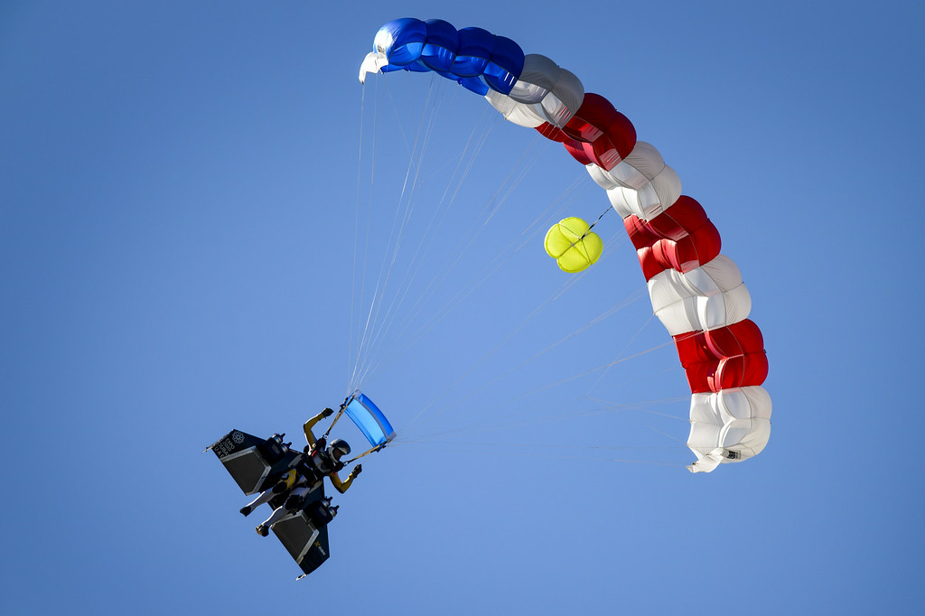 ". Swiss pilot Yves Rossy known as the ""Jetman\"" lands with a parachute after his flight with his jet-powered two meters wingspan wing attached to his back during the first day of the AIR14 air show on August 30, 2014 in Payerne, western Switzerland.  AFP PHOTO / FABRICE  COFFRINI/AFP/Getty Images"