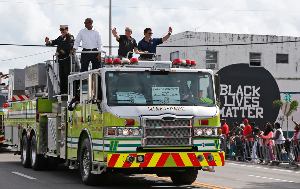 . Miami-Dade County Mayor Carlos Gimenez, second from right, waves from atop a fire truck during a parade honoring Dr. Martin Luther King Jr., Monday, Jan. 16, 2017, in the Liberty City neighborhood of Miami. (AP Photo/Wilfredo Lee)
