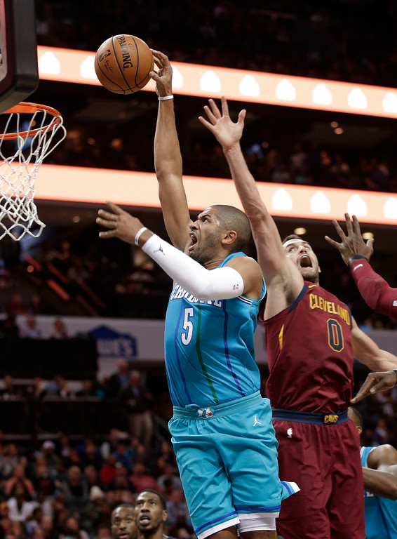 . Charlotte Hornets\' Nicolas Batum (5) drives past Cleveland Cavaliers\' Kevin Love (0) during the first half of an NBA basketball game in Charlotte, N.C., Wednesday, Nov. 15, 2017. (AP Photo/Chuck Burton)