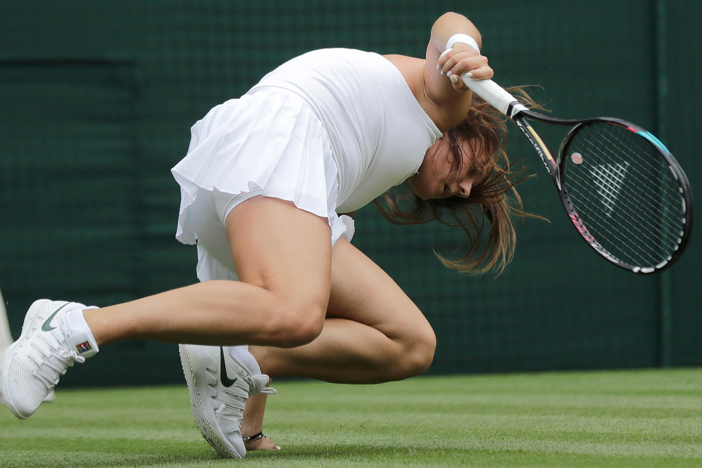. Russia\'s Daria Kasatkina stumbles while returning the ball to Germany\'s Angelique Kerber during their women\'s singles quarterfinals match at the Wimbledon Tennis Championships, in London, Tuesday July 10, 2018. (AP Photo/Ben Curtis)