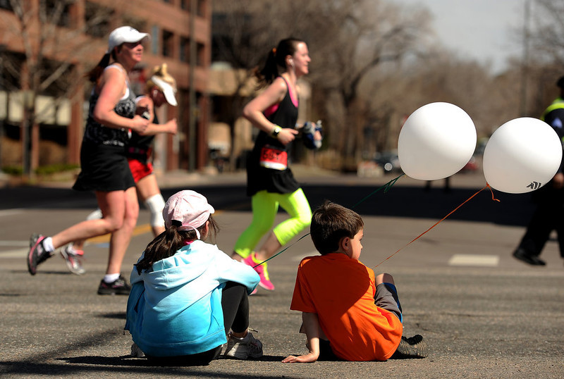 . Lauren Peterson, 6, in blue, and Carter Billings, 7, both of Parker, watch runners in the 5 mile race as they wait for their mothers to run by.  The 31st annual Cherry Creek Sneak had all sorts of distances for this year\'s race.  The Sneak, as it is affectionately named, had a 10 mile, 5 mile, 3.1 mile or 5K, a 1.5 mile Denver\'s 7 Sprint, and a kid\'s fun run for thousands of competitors, runners and walkers that turned out in the Cherry Creek neighborhood of Denver, CO on April 28, 2013.  The race is always held the last Sunday in April. This year participants cheered the national anthem and observed a moment of silence for victims of the Boston Marathon bombing at the start of each race. (Photo by Helen H. Richardson/The Denver Post)