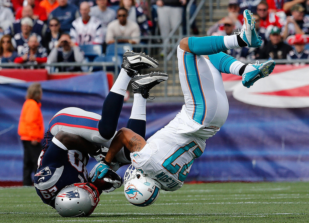 . Jimmy Wilson #27 of the Miami Dolphins stops the run of LeGarrette Blount #29 of the New England Patriots in the first quarter at Gillette Stadium on October 27, 2013 in Foxboro, Massachusetts. (Photo by Jim Rogash/Getty Images)