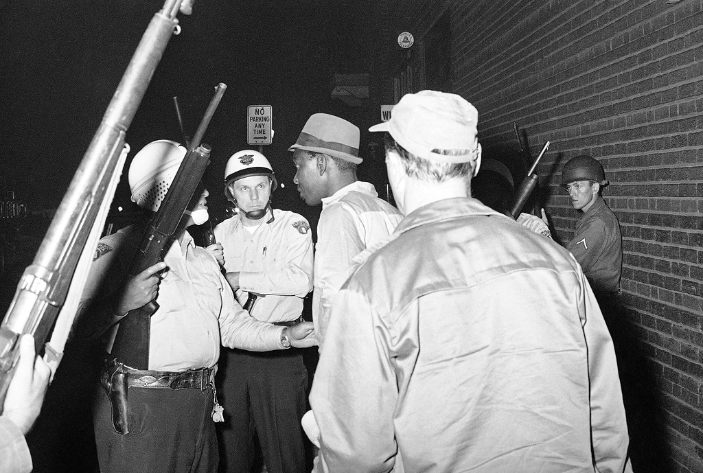 . In case trouble should develop, police officers talk to a man (not identified) whose car was burned in the Hough area in Cleveland, Ohio, July 21, 1966. Police were on hand to help protect firemen fighting the fire near East 101st Street and Hough Avenue. (AP Photo)