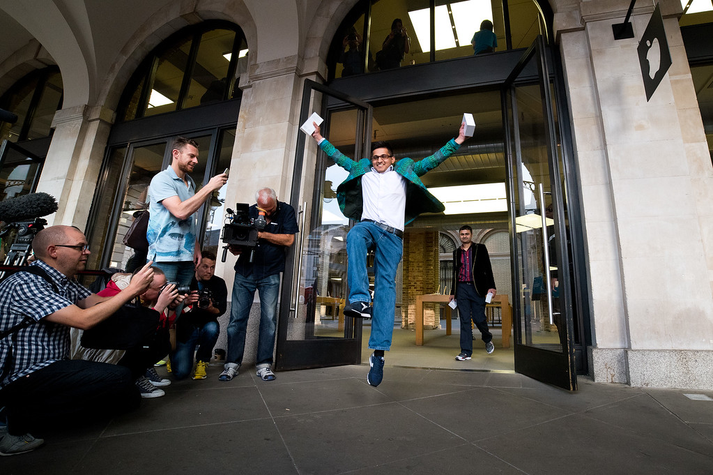 . Jamael Ahmed jumps in the air as he leaves the store after being the first to purchase the iPhone 6 at Apple Covent Gardens launch on September 19, 2014 in London, England.  (Photo by Ben A. Pruchnie/Getty Images)