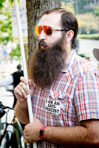 """A counterprotester, carrying a sign and wearing a """"I AM AN ANTI-FASCIST"""" sticker marches and chants across the street from the """"Liberty or Death"""" rally."""