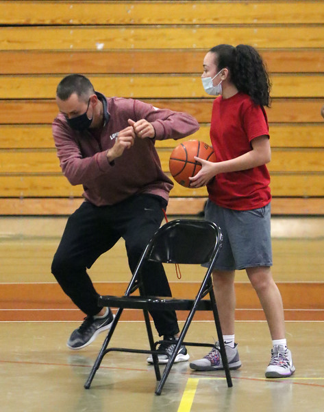 Lowell High girls basketball practice. Head coach Dan Sargent demonstrates a move, as sophomore Deborah Garcia watches. (SUN/Julia Malakie)