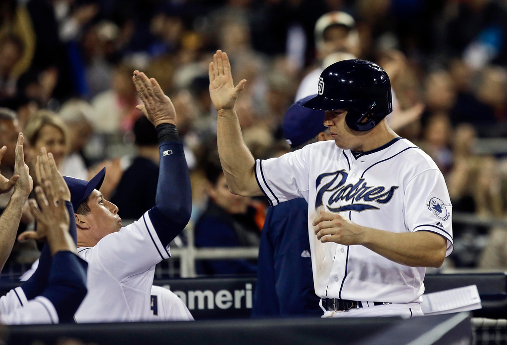 . San Diego Padres\' Nick Hundley, right, is congratulated by teammates after scoring and driving in a run against the Colorado Rockies in the seventh inning of a baseball game Friday April 12, 2013 in San Diego. (AP photo/Lenny Ignelzi)