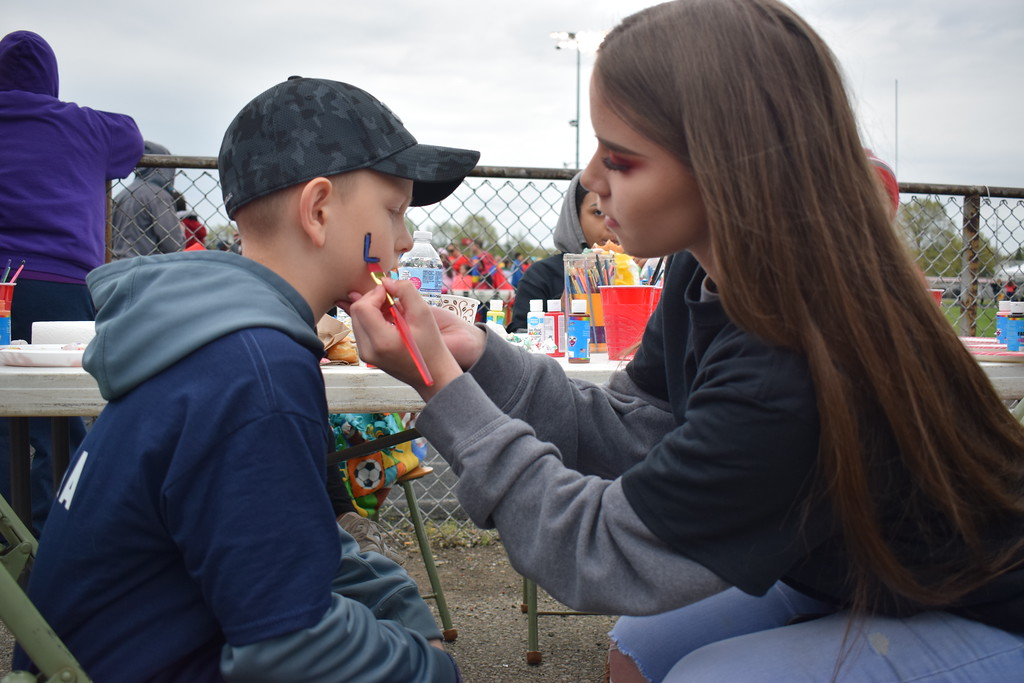 """. Briana Contreras � The Morning Journal <br> Elyria High School Junior, Angelica Conard paints a blue Lorain City School\'s \""""L\"""" on 9-year-old Luke Radanovich\'s cheek while cheering on his sister Mila Radanovich, 15, of Lorain at the 38th Annual Lorain County Special Olympics Track and Field Event held on May 11 at Ely Stadium in Elyria."""
