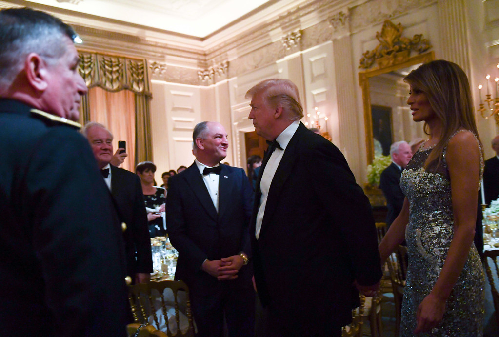 . President Donald Trump, center, and first lady Melania Trump, right, walk into the State Dining Room to attend a State Dinner with French President Emmanuel Macron at the White House in Washington, Tuesday, April 24, 2018. (AP Photo/Susan Walsh)