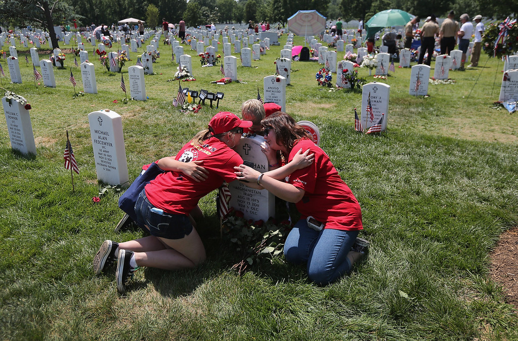 ". Leanne McCain (R), and her children of North Pole, Alaska embrace over her slain husband\'s grave at the National Cemetery on May 28, 2012 in Arlington, Virginia. Her husband and father of four, Army SFC Johnathan McCain, was killed by a roadside bomb in Afghanistan in November 2011. She brought her children this year to take part in a TAPS ""Good Grief Camp\"". Five hundred military children and teens, many of whom had a parent that was killed in the Afghan and Iraq wars, attended the annual four-day \""Good Grief Camp\"" in Arlington, VA and Washington, DC, which is run by TAPS (Tragedy Assistance Program for Survivors). The camp helped them learn coping skills and build relationships so they know they are not alone in the grief of their loved one. They met others of their own age group, learned together and shared their feelings, both through group activities and one-on-one mentors, who are all active duty or former military service members. Some 1,200 adults, most of whom are grieving parents and spouses, also attend the National Military Survival Seminar held concurrently with the children\'s camp. The TAPS slogan is \""Remember the Love. Celebrate the Life. Share the Journey.\""  (Photo by John Moore/Getty Images)"