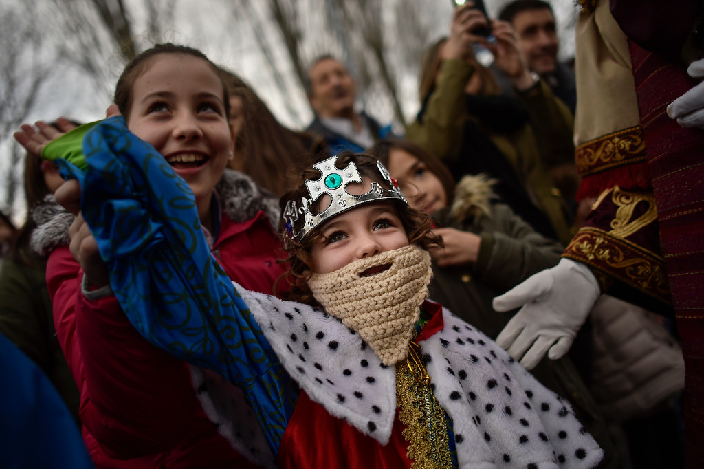 . A boy wearing a crown watches the Cabalgata Los Reyes Magos (Cavalcade of the three kings) the day before Epiphany, in Pamplona, northern Spain, Tuesday, Jan. 5, 2016. It is a parade symbolizing the coming of the Magi to Bethlehem following the birth of Jesus. In Spain and many Latin American countries Epiphany is the day when gifts are exchanged. (AP Photo/Alvaro Barrientos)