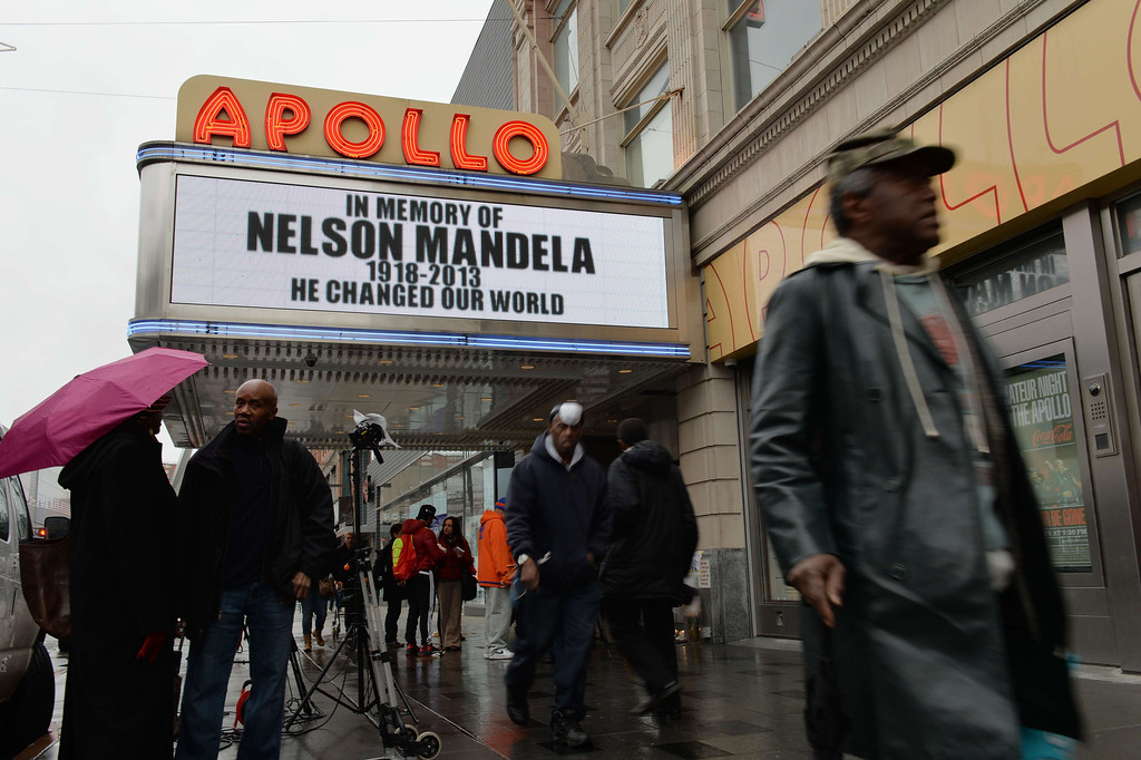 """. The marquee at the Apollo Theater in Harlem displays a memorial sign after the death of Nelson Mandela, former South African president and anti-apartheid leader, on December 6, 2013 in New York. The world on Friday mourned Mandela, who was hailed universally as an \""""incredible gift\"""" to humanity. Mandela\'s \""""rainbow nation\"""" awoke to a future without its founding father and its first black president, after he died late on December 5 aged 95 at his Johannesburg home surrounded by friends and family. AFP PHOTO/Stan HONDASTAN HONDA/AFP/Getty Images"""