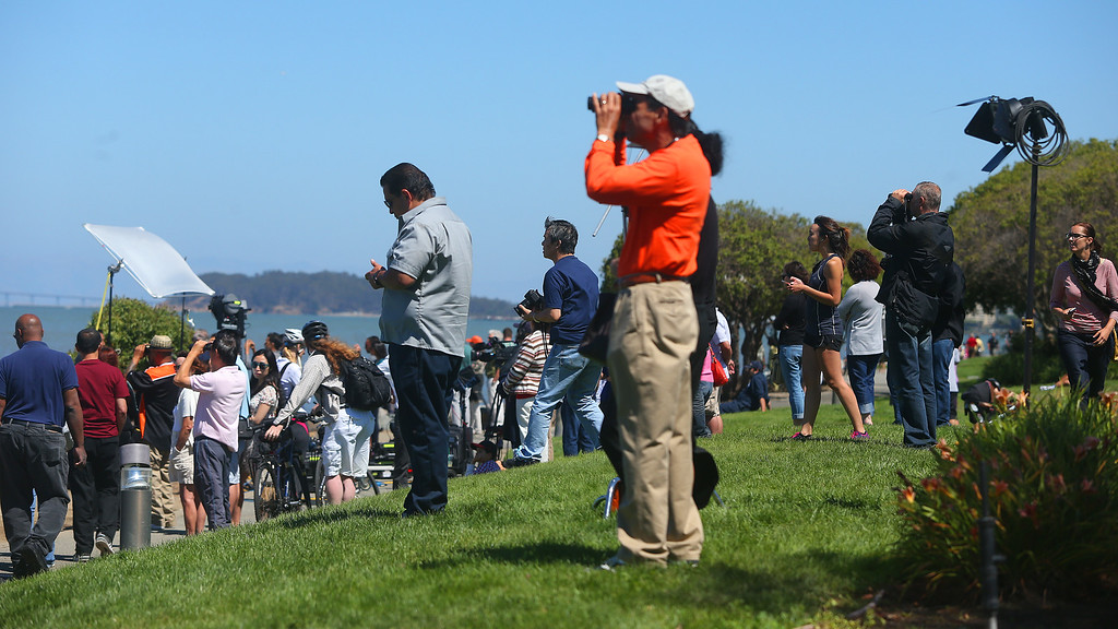 . Onlookers gather along a bayside trail to look at the wreckage of Asiana Airlines Flight 214 at San Francisco International Airport on Sunday, July 7, 2013, in San Francisco, Calif.  The Boeing 777 plane crashed as it was landing at the airport on Saturday killing two passengers and injuring hundreds.   (Aric Crabb/Bay Area News Group)