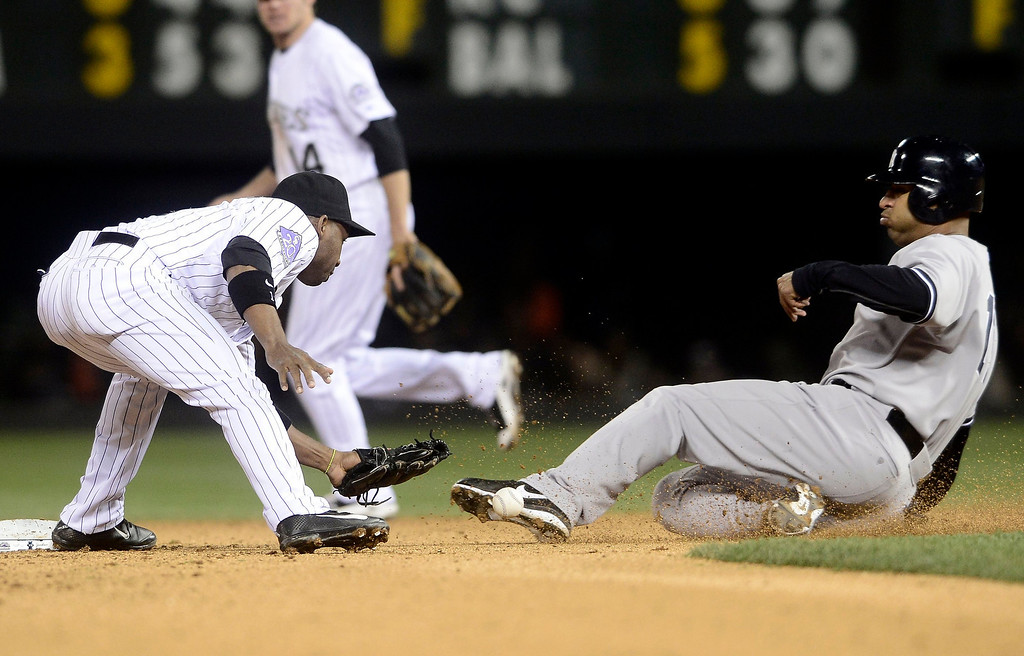 . New York Yankees\' Vernon Wells (R) slides safely into second base as Colorado Rockies\' Jonathan Herrera loses the ball during their inter-league MLB baseball game in Denver, Colorado May 8, 2013.   REUTERS/Mark Leffingwell