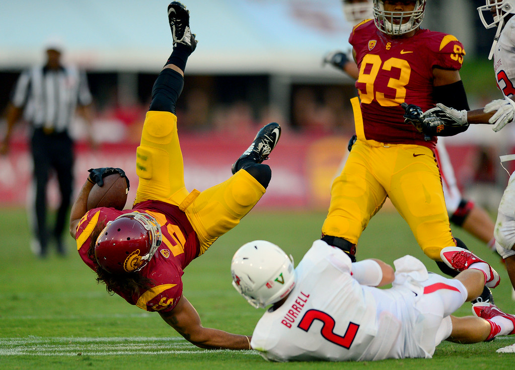 . USC\'s Anthony Sarao is upended by Fresno State\'s Brian Burrell after Sarao\'s third-quarter interception, Saturday, August 30, 2014, at the L.A. Memorial Coliseum. (Photo by Michael Owen Baker/Los Angeles Daily News)