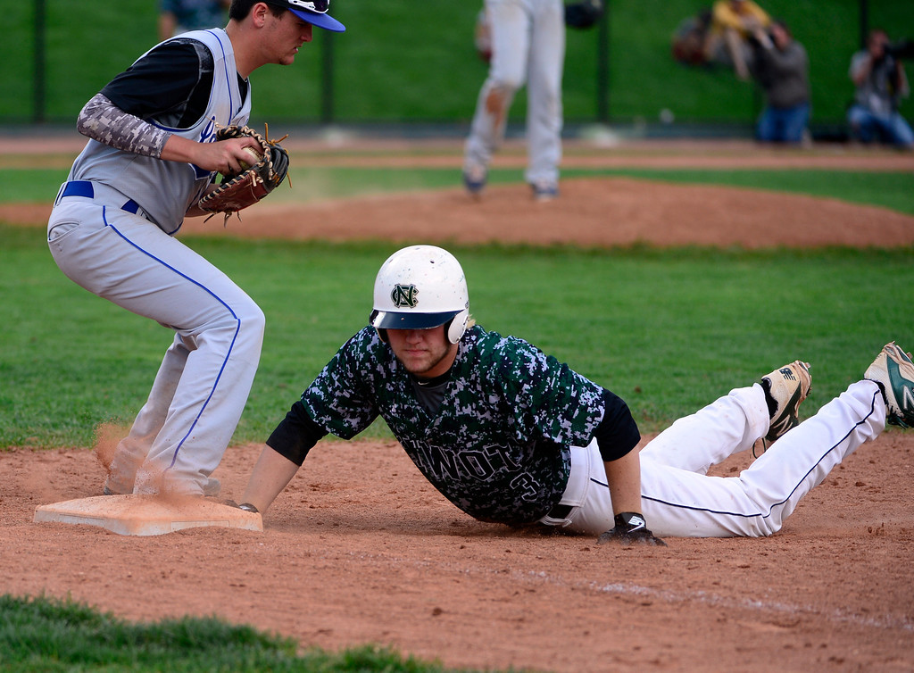 . LAKEWOOD, CO - MAY 23: Niwot\'s Danny Caruso is safe at first base as he dives to the feet of Longmont\'s  Brett Sterkel. The Longmont Trojans take on the Niwot Cougars in the 4A Baseball State Semi-Final Championships. (Kathryn Scott Osler, The Denver Post)
