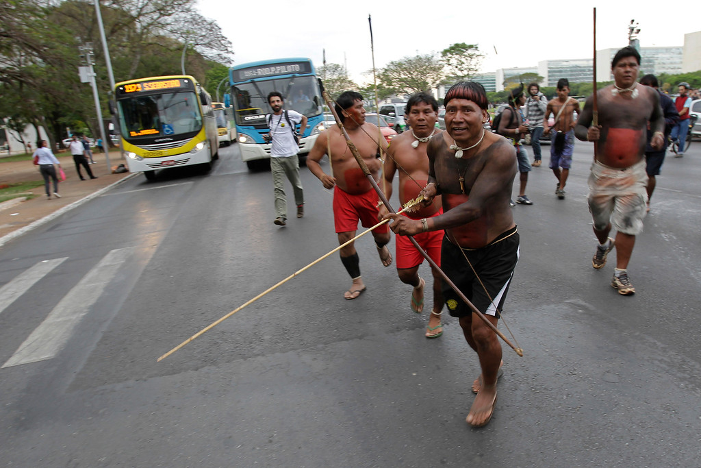 . An Xavante Indian carries a bow and arrow as he crosses the street during the first day of the National Indigenous Mobilization protest in Brasilia, Brazil, Tuesday, Oct. 1, 2013. (AP Photo/Eraldo Peres)