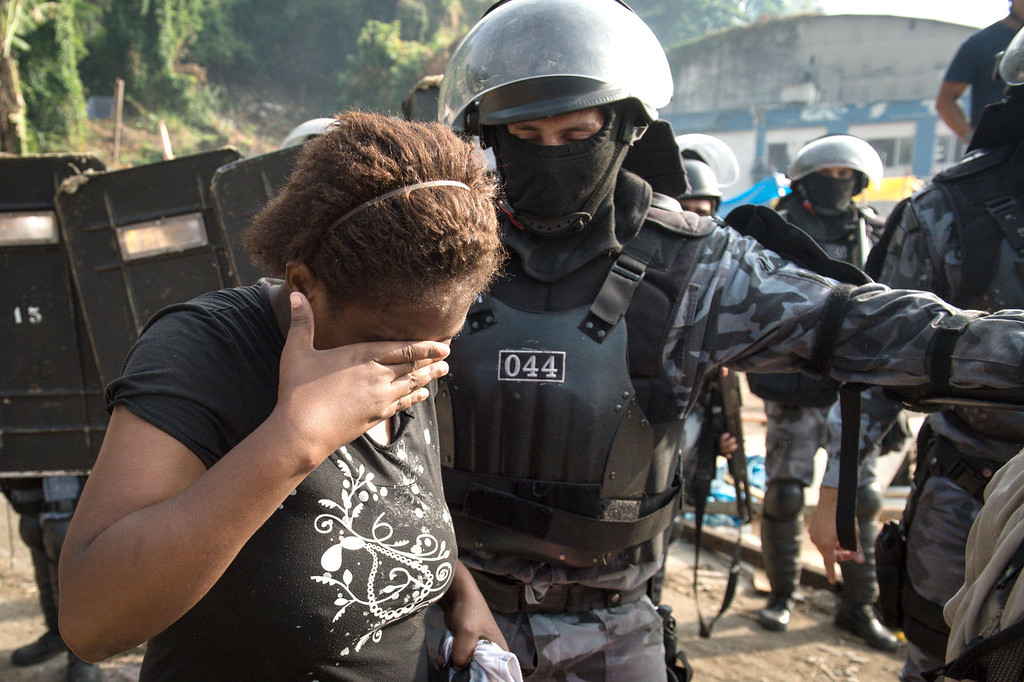 . A woman cries as she has to leave home when police was sent to evict squatters who were occupying an abandoned lot in Rio de Janeiro, Brazil, on April 11, 2014. The lot, owned by a telephone company, included offices and warehouses and was occupied last week. AFP PHOTO/YASUYOSHI CHIBAYASUYOSHI CHIBA/AFP/Getty Images