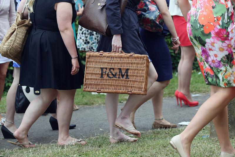 . A racegoer carries a Fortnum & Mason hamper as she walks to Ascot racecourse to attend Royal Ascot on June 20, 2013 in Ascot, England. The \'Royal Ascot\' horse race meeting runs from June 18, 2013 until June 22, 2013 and has taken place since 1711. The racecourse is expected to welcome around 280,000 racegoers over the five days, including Her Majesty The Queen and other members of the Royal Family.  (Photo by Oli Scarff/Getty Images)