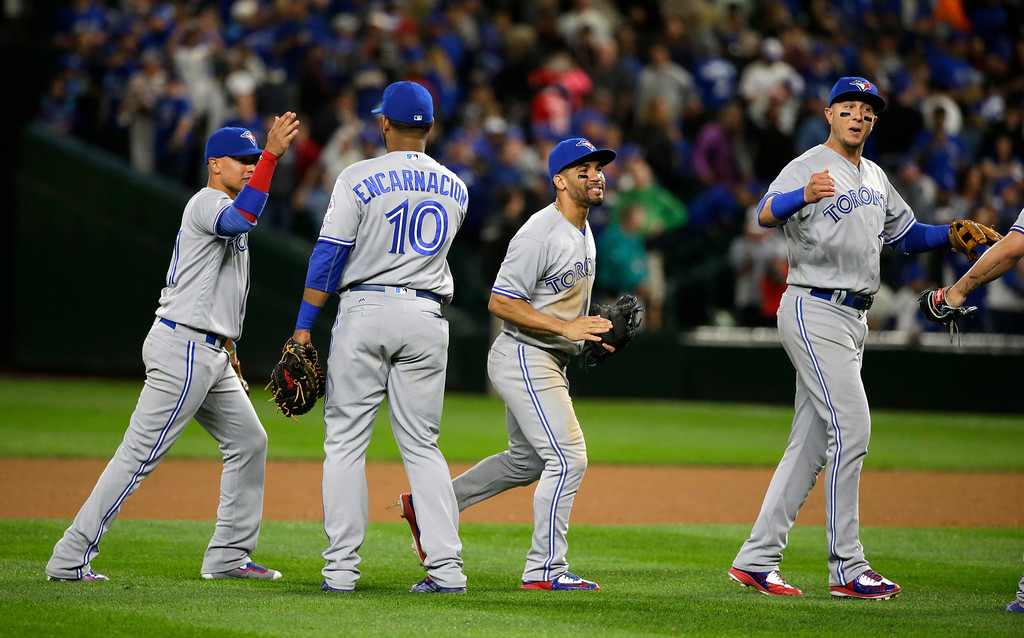 . Toronto Blue Jays players react as they greet teammate Edwin Encarnacion (10) after the Blue Jays beat the Mariners 3-2 in a baseball game, Monday, Sept. 19, 2016, in Seattle. (AP Photo/Ted S. Warren)