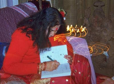 "Shri Mataji autographs a copy of ""The Advent,"" Guru Puja, Dollis Hill ashram London, 2 December 1979"