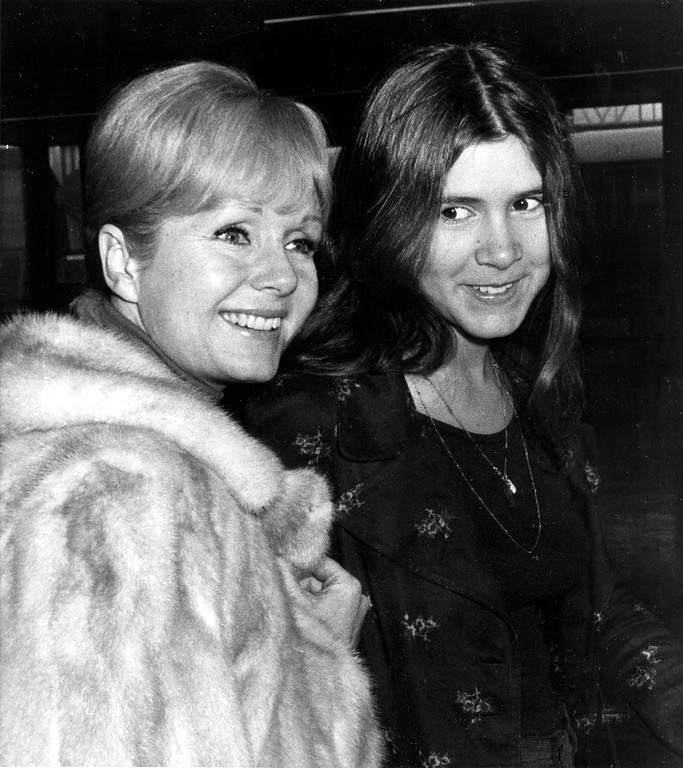 . Actress Debbie Reynolds, left, and her daughter Carrie Fisher, 15, are en route to Madrid at Heathrow Airport in London, England, Feb. 12, 1972.  (AP Photo)