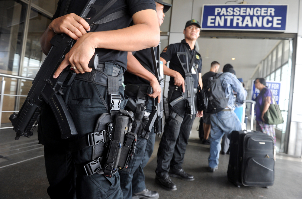 Description of . Heavily armed Philippine anti-terrorist police (L) patrol around Manila's International Airport terminal on March 11, 2014. Revelations that at least two people used stolen passports to board Malaysia Airlines flight MH370, which went missing early on March 8 with 239 people on board after taking off from Kuala Lumpur's international airport, have fuelled fears of a security breach, raising concerns across the region.  (JAY DIRECTO/AFP/Getty Images)