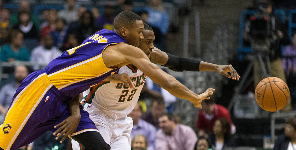 . Milwaukee Bucks\' Khris Middleton battles for a loose ball Los Angeles Lakers\' Wesley Johnson during the first half of an NBA basketball game Thursday, March 27, 2014, in Milwaukee. (AP Photo/Tom Lynn)