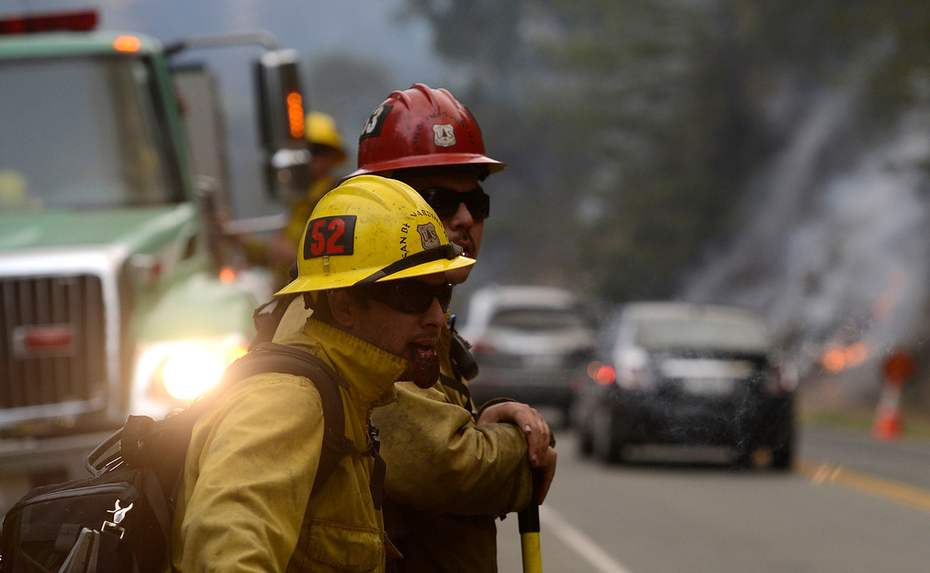 . San Bernadino National Forest Firefighter Aaron Reyes smokes a pipe while standing beside engineer Sal Torres as firefighters light a backfire along Highway 1 between Pfeiffer Ridge Road and the Big Sur Station in Big Sur, Calif. on Wednesday December 18, 2013. (Photo David Royal/ Monterey County Herald)