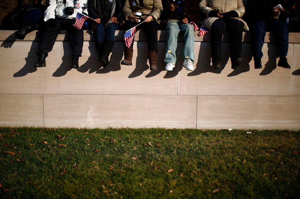 . People sit on a wall at the National Mall before the 57th inauguration ceremonies for U.S. President Barack Obama and Vice President Joe Biden on the West front of the U.S. Capitol, in Washington January 21, 2013. REUTERS/Eric Thayer
