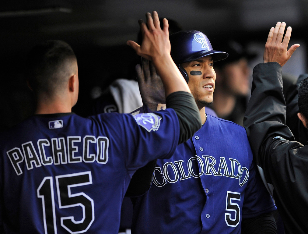 . Colorado Rockies\' Jordan Pacheco high- fives Carlos Gonzalez (5) after Gonzalez and Eric Young Jr. scored on a Troy Tulowitzki double off Tampa Bay Rays starting pitcher David Price during the third inning of a baseball game Saturday, May 4, 2013, in Denver. (AP Photo/Jack Dempsey)
