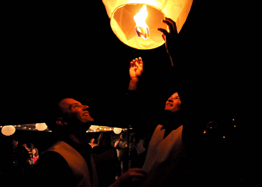. Ryan Pfeifle, left,  and Bradley Weber, right, light a lantern during their wedding ceremony. (Pioneer Press: Sherri LaRose-Chiglo)