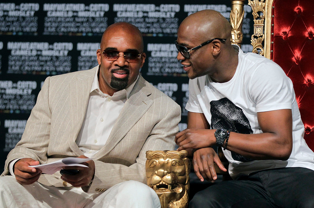 . Floyd Mayweather, right, talks to his adviser Leonard Ellerbe during a news conference Wednesday, May 2, 2012, in Las Vegas. Mayweather and Miguel Cotto are slated to fight for the WBA super welterweight title on Saturday. (AP Photo/Julie Jacobson)