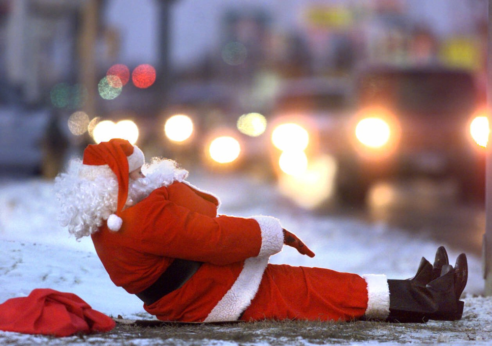 Description of . Santa Claus, a.k.a Lorene Keehr, does stretching exercises to stay warm as she greets passing motorists in front of Simonson Station Store in Grand Forks, N.D., Wednesday, Dec. 23, 1998. (AP Photo/Grand Forks Herald, Eric Hylden)