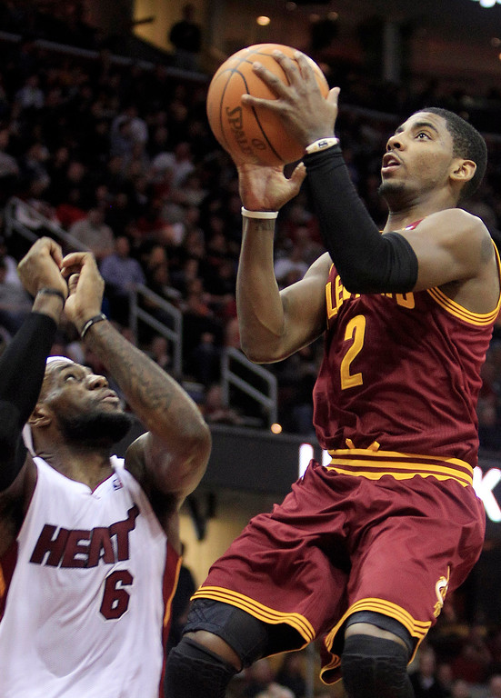 . Cleveland Cavaliers\' Kyrie Irving (2) goes up to the basket against Miami Heat\'s LeBron James (6) during the second quarter of an NBA basketball game on Friday, Feb. 17, 2012, in Cleveland. (AP Photo/Tony Dejak)