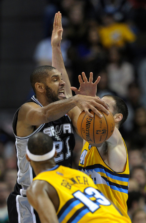 . Spurs forward Tim Duncan (21) tried to work between Corey Brewer and Kosta Koufos in the second half. The Denver Nuggets defeated the San Antonio Spurs 112-106 at the Pepsi Center Tuesday night, December 18, 2012. Karl Gehring/The Denver Post