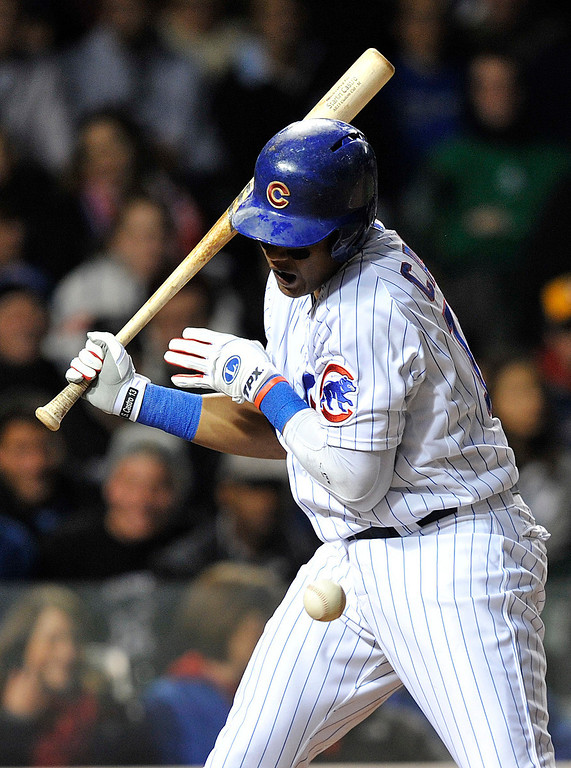 . Chicago Cubs\' Starlin Castro gets hit by a pitch from the Colorado Rockies\' Juan Nicasio during the fourth inning of a baseball game on Monday, May 13, 2013, in Chicago. (AP Photo/Jim Prisching)